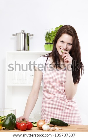 happy young woman nibbling on a chopped cucumber - stock photo