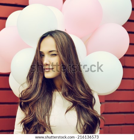 Happy young woman over red brick wall and holding pink and white balloons and gives a wink. Image toned. - stock photo