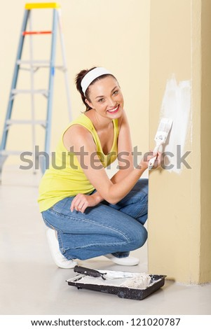 happy young woman painting new home - stock photo