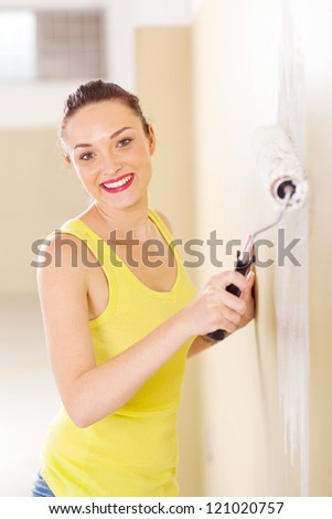 happy young woman painting new home with paint roller - stock photo