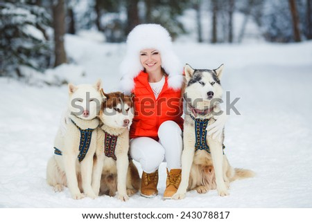 Happy young woman playing with siberian husky dogs in winter forest. Beautiful girl hugging the dog. The girl with the siberian husky - stock photo