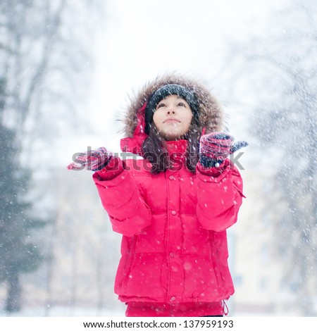 Happy young woman plays with a snow outdoor. Winter day - stock photo