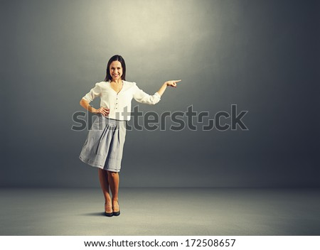 happy young woman pointing at empty copyspace - stock photo