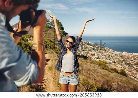 Happy young woman posing with her arms raised to her boyfriend taking her photos with digital camera. Summer vacation fun, young couple hiking in countryside. - stock photo
