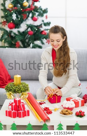 Happy young woman preparing Christmas gift - stock photo