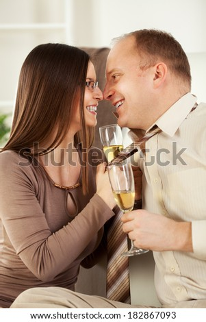 Happy Young woman pulling guy's tie and drinking  champagne. - stock photo