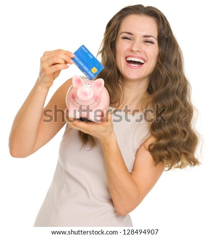 Happy young woman putting credit card into piggy bank - stock photo
