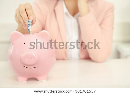 Happy young woman putting dollar banknotes into piggy bank. Money savings concept - stock photo