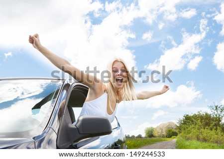 Happy Young Woman Raising Hand Out Of Car Window - stock photo