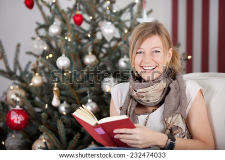 Happy young woman reading a book at Christmas as she sits in front of the Christmas tree looking at the camera with a lovely warm smile - stock photo