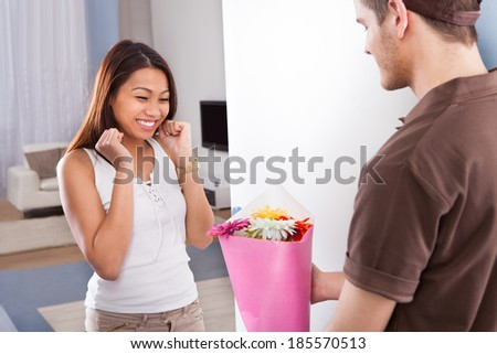 Happy young woman receiving flower bouquet from delivery man at home - stock photo