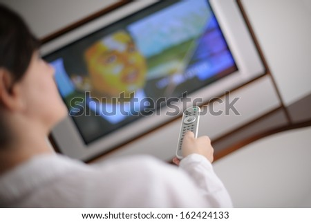 happy young woman relax at home on sofa in bright living room and watching tv - stock photo