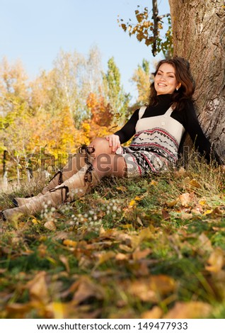 Happy young woman relax in autumn park at the sunny day - stock photo