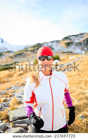 Happy young woman running in mountains on winter fall sunny day, motivation and inspiration fitness contept landscape. Active runner or hiker power walking outdoors in nature, sunset. - stock photo