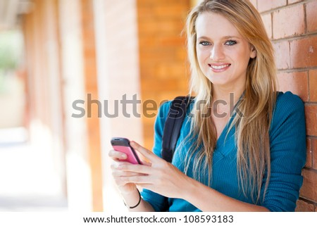 happy young woman sending sms with cell phone - stock photo