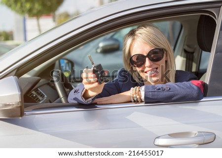 Happy young woman showing her new car keys - stock photo