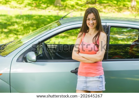 Happy young woman showing new car. - stock photo