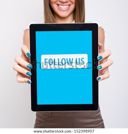 Happy young woman showing tablet computer that states follow us - stock photo