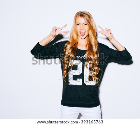 Happy Young Woman Showing Victory Sign and showing tongue On White Background. Indoor. Warm color. Hipster. - stock photo