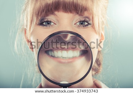 Happy young woman showing white teeth through magnifying glass.  - stock photo