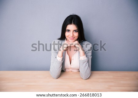 Happy young woman sitting at the table over gray background and looking at camera - stock photo