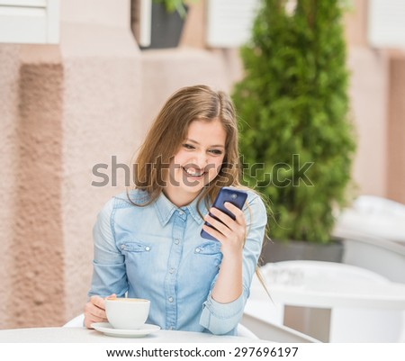 Happy young woman sitting at urban cafe with coffee and using her phone. - stock photo