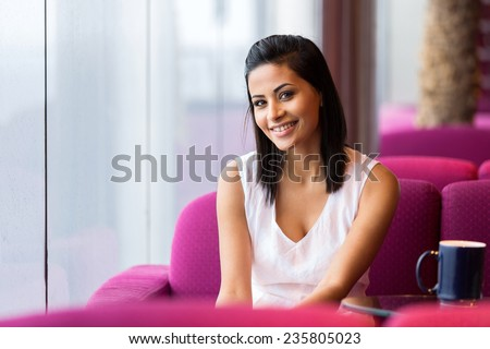 happy young woman sitting in cafe - stock photo