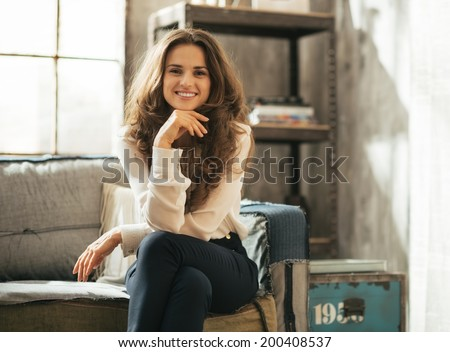 Happy young woman sitting in loft apartment - stock photo