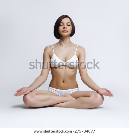 Happy young woman sitting in lotus position - stock photo