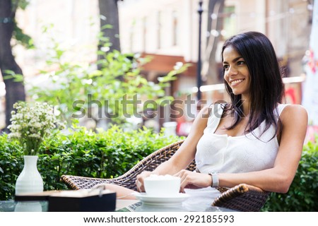 Happy young woman sitting in outdoors cafe with cup of coffee - stock photo