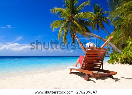 happy young woman sitting on beach chair on tropical beach - stock photo