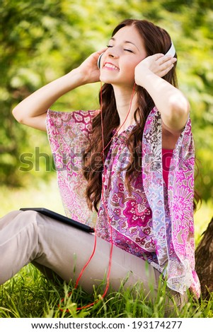 Happy Young Woman sitting on grass in the Beautiful Nature and Listening Music from digital tablet. - stock photo
