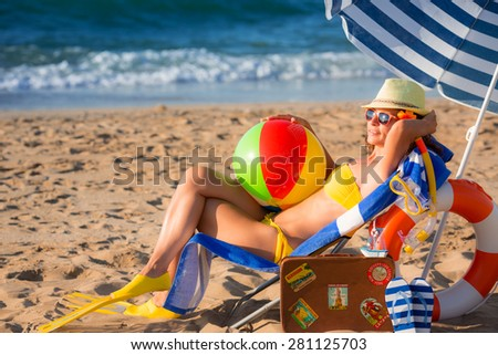 Happy young woman sitting on the beach. Summer vacation concept - stock photo