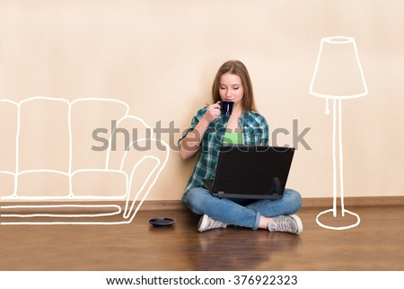 Happy young woman sitting on the floor with crossed legs, using laptop and drinking coffee in empty room with sketched furniture. Young girl in the new flat. Beautiful girl working in empty apartment. - stock photo