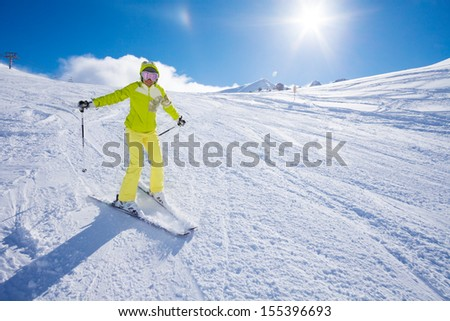 Happy young woman ski in the mountain with her hands lifted expressing enjoyment - stock photo