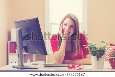 Happy young woman smiling in her home office - stock photo
