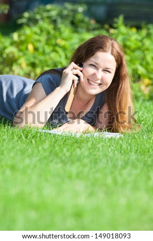 Happy young woman speaking on the phone on green grass meadow. Copyspace - stock photo