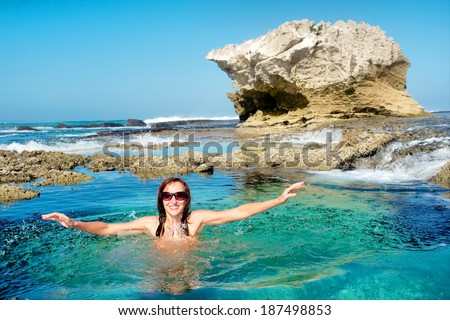 Happy young woman splashes in water on awesome rocky beach. Shot in De Hoop Nature Reserve, Western Cape, South Africa. - stock photo