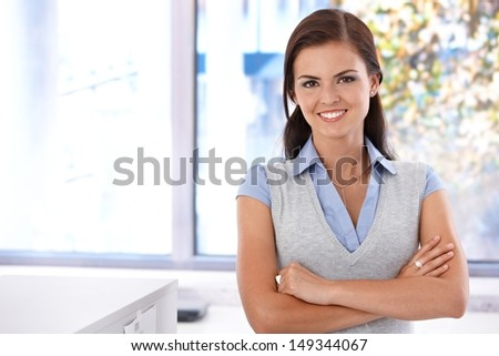 Happy young woman standing arms crossed front of window. - stock photo