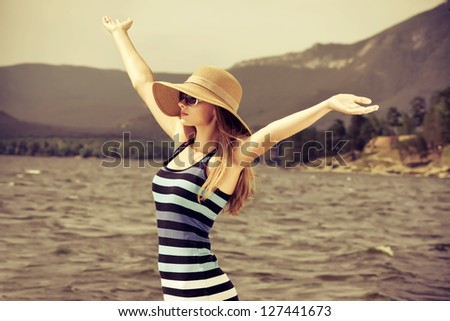 Happy young woman standing face to the wind over beautiful landscape. - stock photo