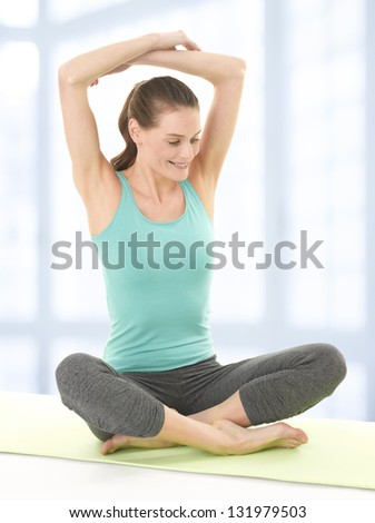 Happy Young Woman Stretching Legs on Yoga Mat. Isolated on white background. - stock photo