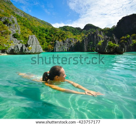Happy young woman swims in the crystal clear water near of amazing forms islands - stock photo