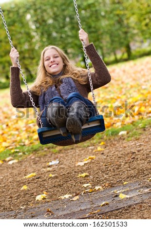 Happy, young woman swinging - stock photo