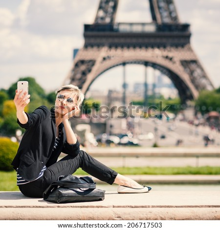 Happy young woman taking a selfie with mobile phone in Paris, France.  - stock photo