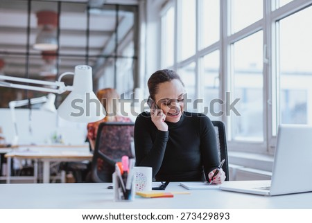 Happy young woman taking notes while talking on mobile phone. African woman working at her desk answering a phone call. - stock photo