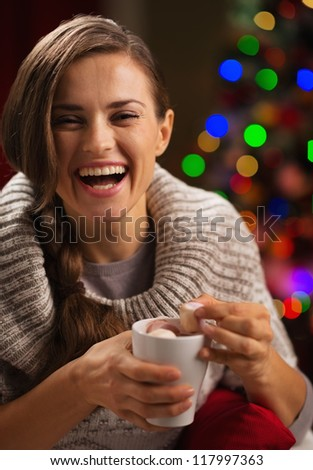 Happy young woman taking out marshmallow from cup of hot chocolate - stock photo