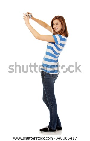 Happy young woman taking selfie with classic slr camera. - stock photo