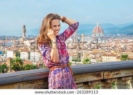 Happy young woman talking cell phone against panoramic view of florence, italy - stock photo
