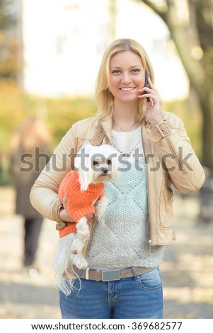 Happy young woman talking on the phone and carrying her cute little dog while walking in a park - stock photo