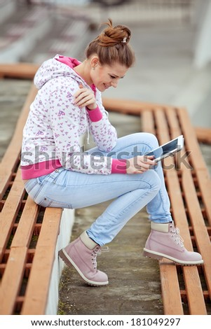 Happy young woman using a tablet computer resting - stock photo